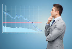Thinking businessman in suit making decision. Business, people, statistics, economics and crisis concept - thinking businessman in suit looking to chart making Stock Images