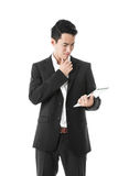 Thinking Businessman using a tablet Stock Image