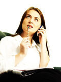 Thinking Businesswoman. A young businesswoman sits with papers in her lap, a cellphone to her ear, and a pencil to her lips as she stares at the ceiling, deep in Stock Image