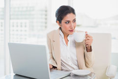 Thinking businesswoman holding cup while working on laptop Stock Photos