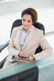 Thinking businesswoman holding tablet Stock Images