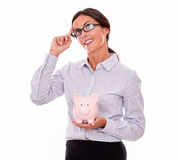 Thinking businesswoman with pink piggy bank Stock Images