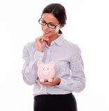 Thinking businesswoman with pink piggy bank Stock Photo