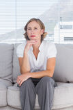 Thinking businesswoman sitting on couch Stock Image