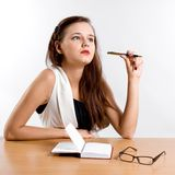 Thinking businesswoman sitting at her desk Stock Images