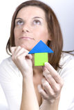 Thinking of buying a new home. Young woman holding a toy house lost in her thoughts Royalty Free Stock Photo