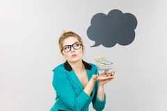 Thinking business woman holding small tiny shopping cart Royalty Free Stock Photography