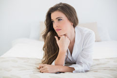 Thinking casual brown haired woman in white pajamas lying on her bed Stock Photography