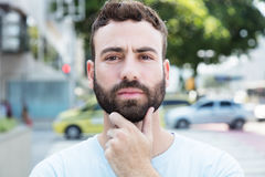 Thinking caucasian man with beard outdoor in city. With streets and buildings in the background Stock Images