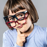 Thinking cheeky little kid trying many eyeglasses hesitating for choice Royalty Free Stock Photography