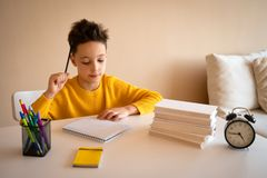 Thinking child bored, frustrated and fed up doing his homework.  stock photos