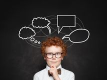 Thinking child boy and empty speech clouds bubbles on chalkboard background. Pensive kid in glasses on school blackboard.  royalty free stock images
