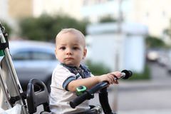 Thinking child on tricycle with push handl Stock Images