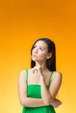 The thinking Chinese girl on yellow background Stock Photos