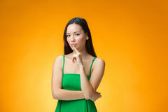 The thinking Chinese girl on yellow background Royalty Free Stock Photos