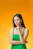 The thinking Chinese girl on yellow background Stock Photo