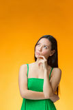 The thinking Chinese girl on yellow background Royalty Free Stock Image