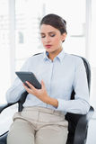 Thinking classy brown haired businesswoman using a calculator. In bright office Stock Image
