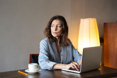 Thinking concentrated woman writer sitting indoors using laptop Stock Image