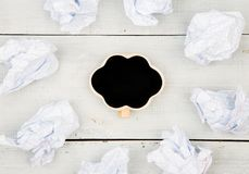 Thinking concept, inspiration, choose the best ideas - crumpled. Paper around a small blackboard in form of cloud on white wooden table Royalty Free Stock Image
