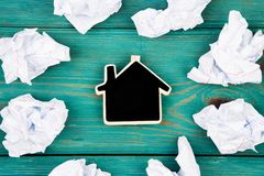 Thinking concept, inspiration, choose the best ideas - crumpled. Paper around a small blackboard in form of house on blue wooden table Stock Photo