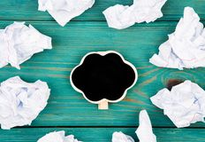 Thinking concept, inspiration, choose the best ideas - crumpled. Paper around a small blackboard in form of cloud on blue wooden table Royalty Free Stock Images