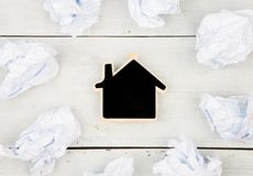 Thinking concept, inspiration, choose the best ideas - crumpled. Paper around a small blackboard in form of house on white wooden table Royalty Free Stock Photos