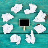 Thinking concept, inspiration, choose the best ideas - crumpled. Paper around a small blackboard in form of rectangle on blue wooden table Royalty Free Stock Photography
