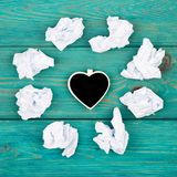 Thinking concept, inspiration, choose the best ideas - crumpled. Paper around a small blackboard in form of heart on blue wooden table Royalty Free Stock Photos