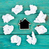 Thinking concept, inspiration, choose the best ideas - crumpled. Paper around a small blackboard in form of house on blue wooden table Royalty Free Stock Photos