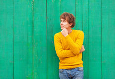 Thinking curly man in yellow sweater and scarf on green wooden background Stock Photography