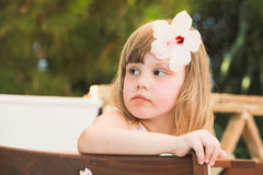 Thinking Cute Caucasian little girl with flower Stock Images