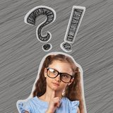 Thinking cute small kid girl in eyeglasses with question and exclamation signs above the head on grey background. stock images