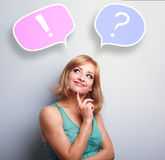 Thinking cute young woman with question and exclamation signs in Royalty Free Stock Photography