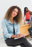 Thinking designer sitting in front of her colleagues using digital tablet Royalty Free Stock Photo