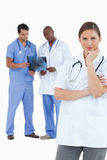 Thinking doctor with colleagues behind her Royalty Free Stock Image