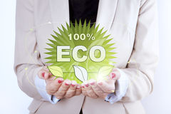 Thinking ECO symbol in woman hands. Help the environment. 100 % ECO symbol - digitally generated in hands of a woman.nSymbol is round and green colour. On the royalty free illustration