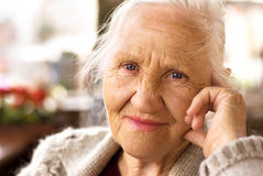 Thinking elderly woman. Portrait of the smiling elderly woman, sitting outdoor stock images