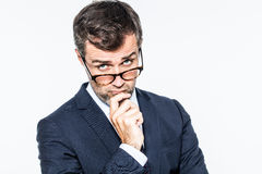 Thinking far-sighted middle aged businessman with eyeglasses down stock photo