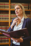 Thinking female librarian holding textbook. In library Stock Photo