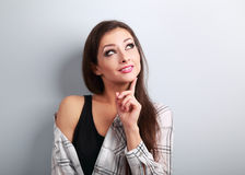 Thinking fun casual smiling young woman looking up on blue backg Stock Photography