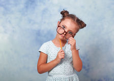Thinking fun kid girl in glasses looking happy and holding eyegl Royalty Free Stock Photography