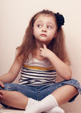 Thinking fun kid girl sitting in jeans and looking Royalty Free Stock Images