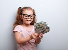 Thinking fun small kid girl in glasses counting money in the han Stock Photography