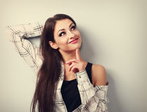 Thinking fun smiling young woman in casual clothing looking up. Stock Images