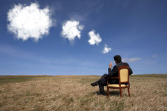 Thinking about the future. Businessman sitting in a chair thinking about the future the field