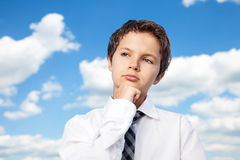 Thinking about the future. Boy in white shirt and a tie resting his chin on his right fist looking thoughtful. He is outside, with background a beautiful blue Royalty Free Stock Image