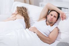 Thinking about future. Man is lying in bed with girlfriend and thinking Stock Images
