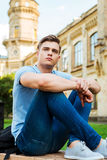 Thinking about future. Thoughtful male student sitting on the bench and looking away with university building in the background Stock Image