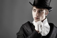 Thinking gentlemen. Portrait of a young gentlemen wearing dinner jacket and black top hat. Shot in a studio Royalty Free Stock Images